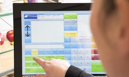 Hand vor Computerbildschirm, Zeigefinger wählt am Touchscreen etwas aus