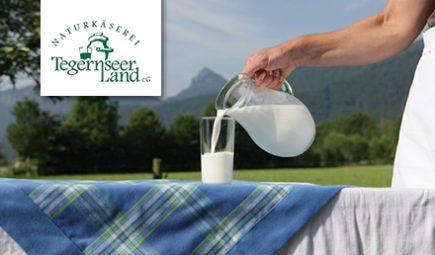Logo Naturkäserei Tegernseer Land. Tisch mit Glas, in das Milch eingeschenkt wird.